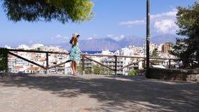 La donna turistica in cappello di paglia gode del sole in piattaforma di osservazione, il panorama di Agios Nikolaos, Creta stock footage