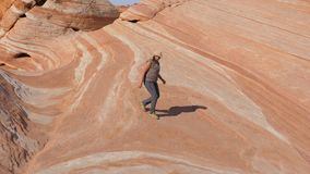 La donna turistica discende dalla cima della collina sulle rocce rosse di pietra colorate Fotografie Stock Libere da Diritti