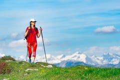 La donna turistica si è vestita nel rosso con le alte montagne con neve Immagini Stock