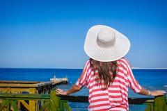 La donna in un grande cappello bianco esamina il mare fotografia stock libera da diritti