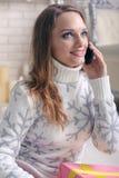La donna in un maglione caldo parla sul telefono fotografia stock libera da diritti