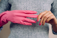La donna in un maglione grigio rimuove il primo piano rosa dei guanti di pulizia Immagine Stock