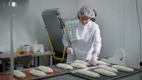 La donna in un negozio di dolci Il castana in una forma bianca fa le preparazioni per la torrefazione del pane La ragazza del med stock footage