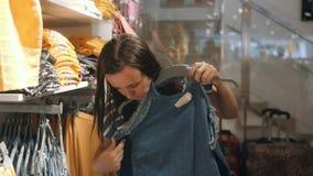 La donna in un negozio di vestiti sceglie le prendisole del denim stock footage