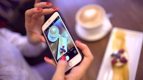 La donna in un ristorante fa la foto di alimento con la macchina fotografica del telefono cellulare Chiuda su delle mani con lo s stock footage