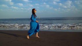 La donna in un vestito blu funziona lungo una spiaggia vulcanica nera Movimento lento stock footage