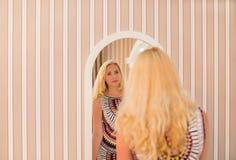 La donna in un vestito guarda nello specchio Immagini Stock Libere da Diritti