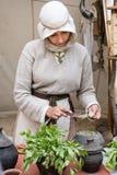 La donna in un vestito medievale spande il burro sul pane con un corteggiare immagine stock libera da diritti