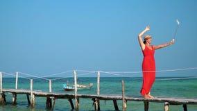La donna in un vestito rosso ed in un cappello è fotografata sul bastone di Selfie La donna cammina su un pilastro con il bastone archivi video