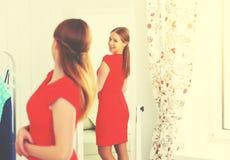 La donna in un vestito rosso guarda nello specchio immagine stock libera da diritti