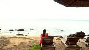 La donna in un vestito rosso si siede sulla banca di un'isola tropicale La donna su un letto della plancia in mezzo alle palme video d archivio