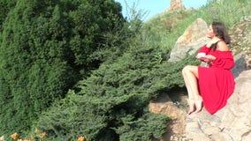 La donna in un vestito rosso sta sedendosi su una roccia archivi video