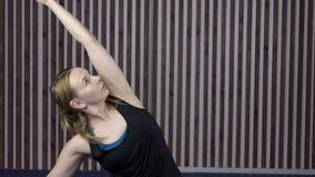 La donna in una maglietta nera allunga il suo braccio durante le classi della ginnastica stock footage