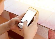 La donna utilizza il suo telefono cellulare all'aperto, alto vicino fotografia stock