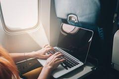 La donna utilizza un computer portatile mentre su un aereo Fotografia Stock Libera da Diritti