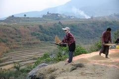 La donna vaglia il grano nel Bhutan rurale Fotografie Stock Libere da Diritti