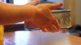 La donna vaglia la farina al un setaccio stock footage