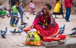 La donna vende i semi del cereale sul mercato di strada nepalese Fotografia Stock Libera da Diritti