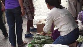 La donna vende le verdure lungo il marciapiede della città video d archivio