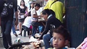 La donna vende le verdure lungo il marciapiede sporco della città stock footage