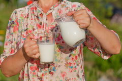 La donna versa il latte in vetro Immagine Stock