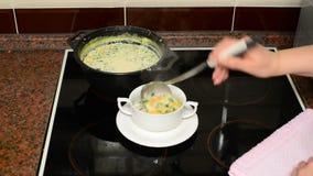 La donna versa la minestra del formaggio in ciotola stock footage