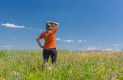 La donna in vestiti di allenamento ammira il campo selvaggio dell'estate Immagine Stock Libera da Diritti