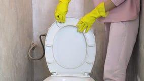 La donna in vestiti domestici pulisce la toilette stock footage