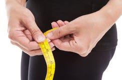 La donna in vestiti neri che misurano la sua anca con nastro adesivo di misurazione immagine stock libera da diritti