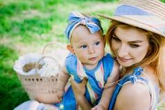 La donna in vestito blu alza sulla sua piccola figlia negli stessi vestiti Fotografie Stock