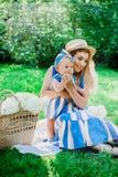 La donna in vestito blu alza sulla sua piccola figlia negli stessi vestiti Immagini Stock Libere da Diritti