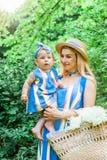 La donna in vestito blu alza sulla sua piccola figlia negli stessi vestiti Fotografia Stock