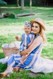 La donna in vestito blu alza sulla sua piccola figlia negli stessi vestiti Fotografie Stock Libere da Diritti