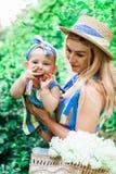 La donna in vestito blu alza sulla sua piccola figlia negli stessi vestiti Immagini Stock