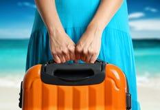 La donna in vestito blu tiene la valigia arancio in mani sulla spiaggia Fotografie Stock