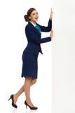 La donna in vestito convenzionale sta spingendo una grande insegna Fotografie Stock