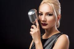 La donna in vestito di cuoio nero tiene un microfono del metallo immagine stock
