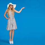 La donna in vestito e cappello di Sun punteggiati bianco sta stando la punta dei piedi ed indicare Fotografie Stock