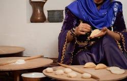 La donna in vestito nazionale, prepara le pasticcerie tradizionali di Shekerbura fotografia stock libera da diritti