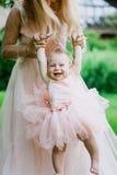 La donna in vestito rosa alza sulla sua piccola figlia negli stessi vestiti in parco Fotografie Stock Libere da Diritti