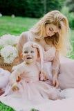 La donna in vestito rosa alza sulla sua piccola figlia negli stessi vestiti in parco Fotografia Stock Libera da Diritti
