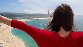 La donna in vestito rosso gode di una vista della costa dell'oceano vicino a Nazare, Portogallo Movimento lento stock footage