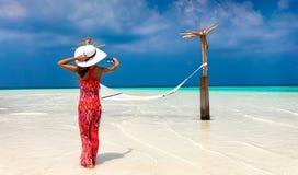 La donna in vestito rosso prende una foto di una regolazione della spiaggia in Maldive fotografie stock libere da diritti