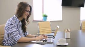 La donna in vetri con piacere lavora per i computer portatili con un ufficio video d archivio