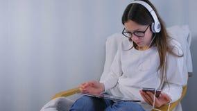 La donna in vetri e cuffie fa gli acquisti nel deposito online facendo uso dello smartphone e della compressa che si siedono in p stock footage
