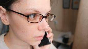 La donna in vetri sta parlando il telefono cellulare e sta guardando avanti Primo piano del fronte video d archivio