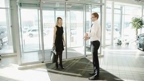 La donna viene alla sala d'esposizione in cui è al benvenuto della porta al commerciante stock footage