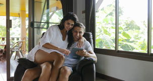 La donna viene a equipaggiare il touch screen di conversazione del computer di Sit In Armchair Using Tablet che passa in rassegna video d archivio