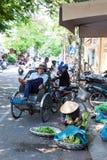 La donna vietnamita in cappello conico tradizionale sta ordinando i verdi immagini stock
