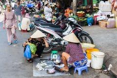 La donna vietnamita in cappello conico tradizionale sta vendendo il pesce immagini stock libere da diritti